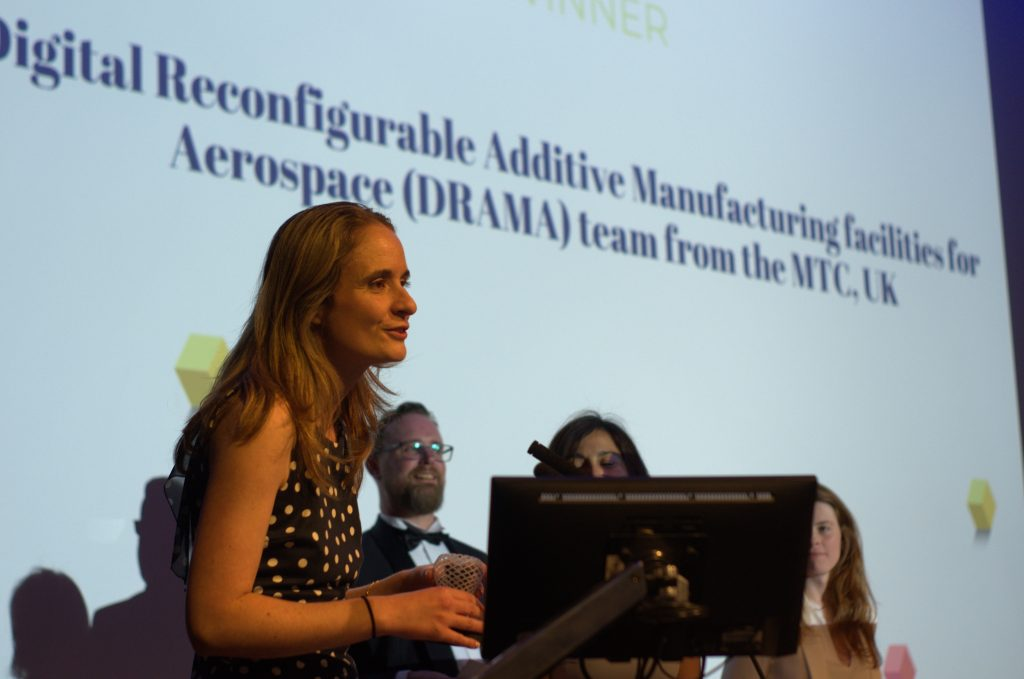 Katy Milne Chief Engineer of the Digital Reconfigurable Additive Manufacturing facilities for Aerospace (DRAMA) project at MTC accepts the 2019 Academic/Research Team of the Year award on behalf of her team. Photo by 3D Printing Industry