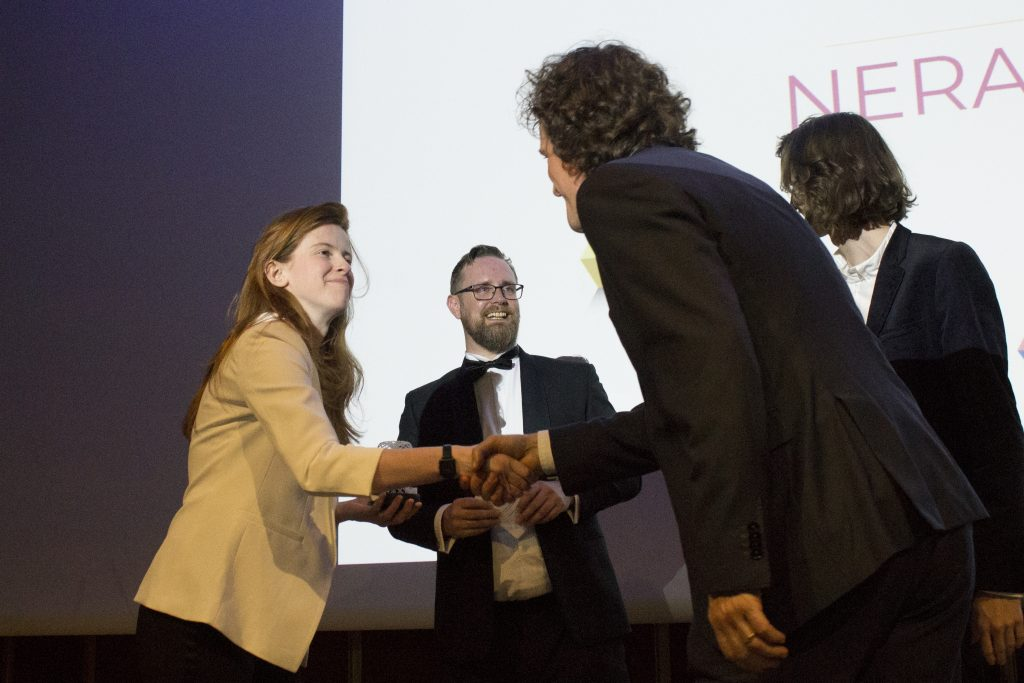 Beau Jackson, Senior Journalist, 3D Printing Industry, shakes hands with Jan Hoffman, Head Of Software at BigRep GmbH winner of 2019 Creative Use of 3D Printing. This year, the trophy was awarded for BigRep's development of the 3D printed NERA e-motorcycle. Photo by 3D Printing Industry