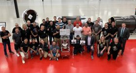 The team of Rocket Lab celebrating the 100th 3D print of the Rutherford engine. Image via Rocket Lab.