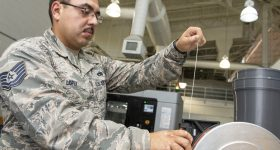 U.S. Air Force Tech. Sgt. Rogelio Lopez, 60th Maintenance Squadron assistant aircraft metals technology section chief, loads Ultem 9085 material for Stratasys F900. Photo via U.S. Air Force photo/Louis Briscese.