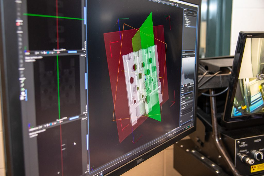 3D rendering of an antilock braking system imaged by the X-ray CT system. Red and green planes represent slices and sections from different viewpoints used to observes the part's internal structure. Photo via Auburn University