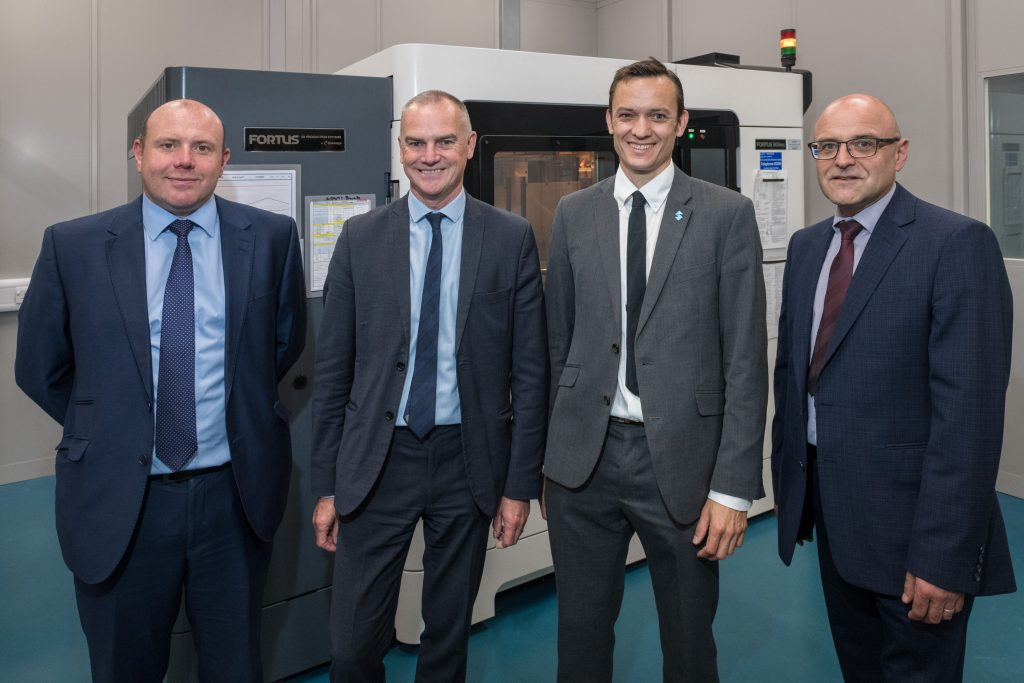From L - R: Ian Barton, Head of Strategy & Investment Planning, BAE Systems; Andrew Schofield, Head of Manufacturing & Materials Engineering, BAE Systems; Yann Rageul, Head of Strategic Accounts for EMEA at Stratasys; and Simon Whitaker, Technology Operations Manager at BAE Systemsin front of the Stratasys F900 3D printer. Photo via Stratasys