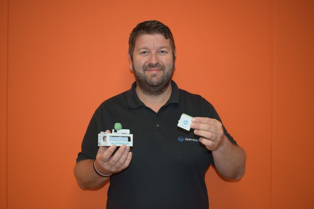 James Blackburn, Sales Director at GoPrint3D, holds two full color 3D prints from the HP Jet Fusion 300/500 series. Photo via HP