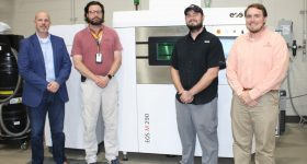 Team members from NCAME, Huntsville City Schools, and EOS worked together to bring online the district's second industrial 3D printer at Grissom High School. Photo via Auburn University.