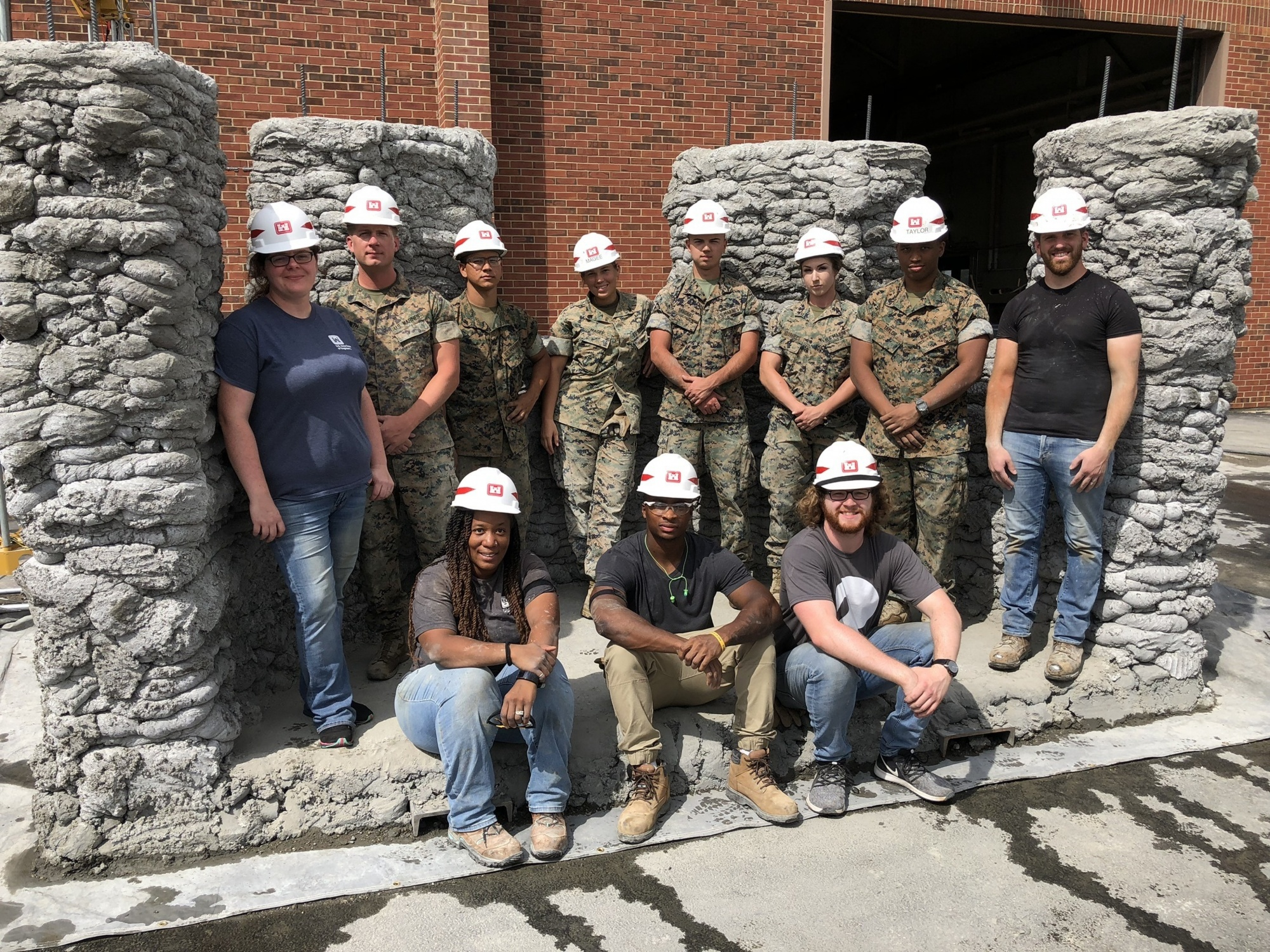 Marines from 7th Engineer Support Battalion along with engineers from the U.S. Army Corps of Engineers Construction Engineering Research Laboratory pose with a concrete bunker during a 3D concrete printing exercise. Photo via U.S. Marines/Staff Sgt. Michael Smith, 7th ESB.