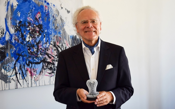 Dr. Hans Langer, founder of EOS, and the 2019 3D Printing Industry trophy for Outstanding Contribution to 3D Printing. Photo via EOS