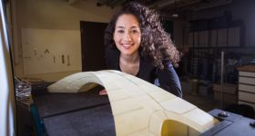 Karly Bast beside the 3D printed model of da Vinci's bridge design. Photo via MIT.