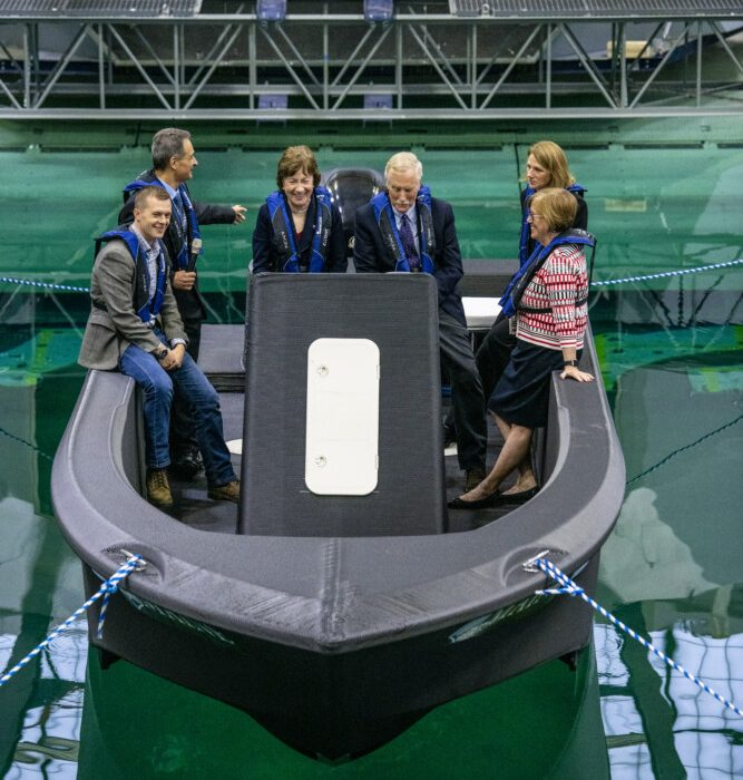 Members of Maine's congressional delegation – Sens. Susan Collins and Angus King, (helm) and Rep. Jared Golden, left – join Habib Dagher, director of University of Maine's Advanced Structures and Composites Center, on the maiden voyage of 3Dirigio in a wave simulation tank at the Orono campus. They are joined by University of Maine President Joan Ferrini-Mundy, right and Valri Lightner, from the Advanced Manufacturing Office at the Department of Energy. Photo via Sun Journal.