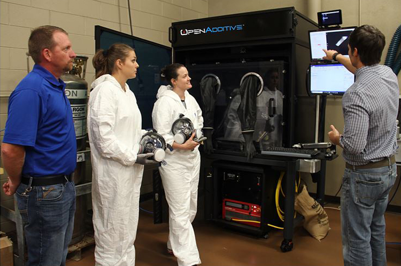 Eric Wooldridge explains to students and Curtis Cash, SCC professor of Machine Tool Technology, how the OpenAdditive PANDA System operates. Photo via SSC.