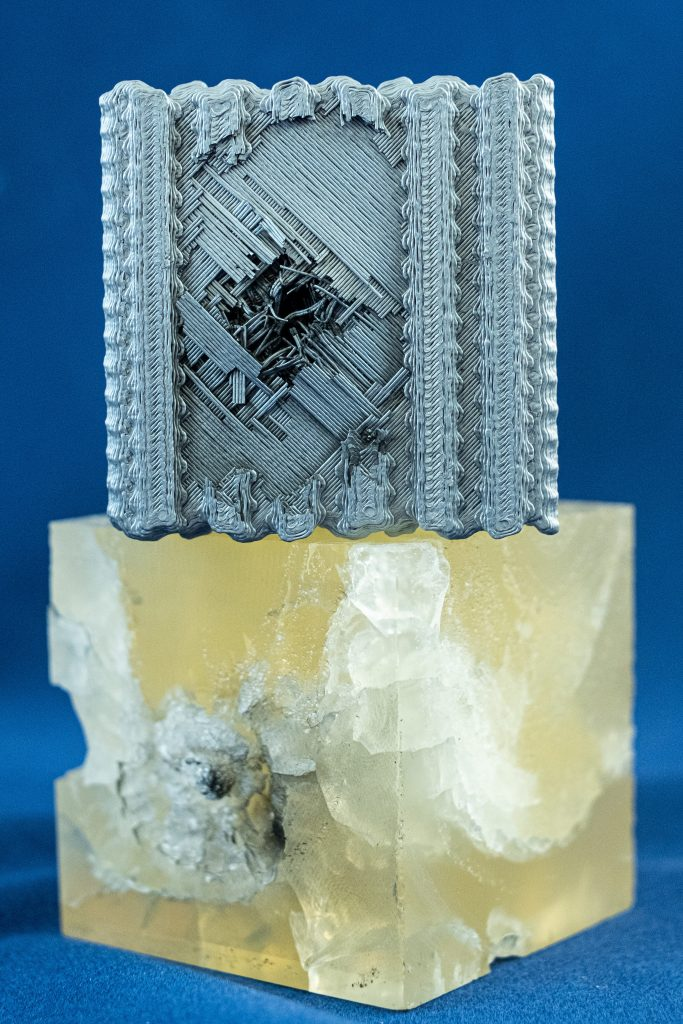 A tubulane-like polymer cube created at Rice University (in grey) post impact, compared to a solid block of the same material post projectile impact. Photo by Jeff Fitlow