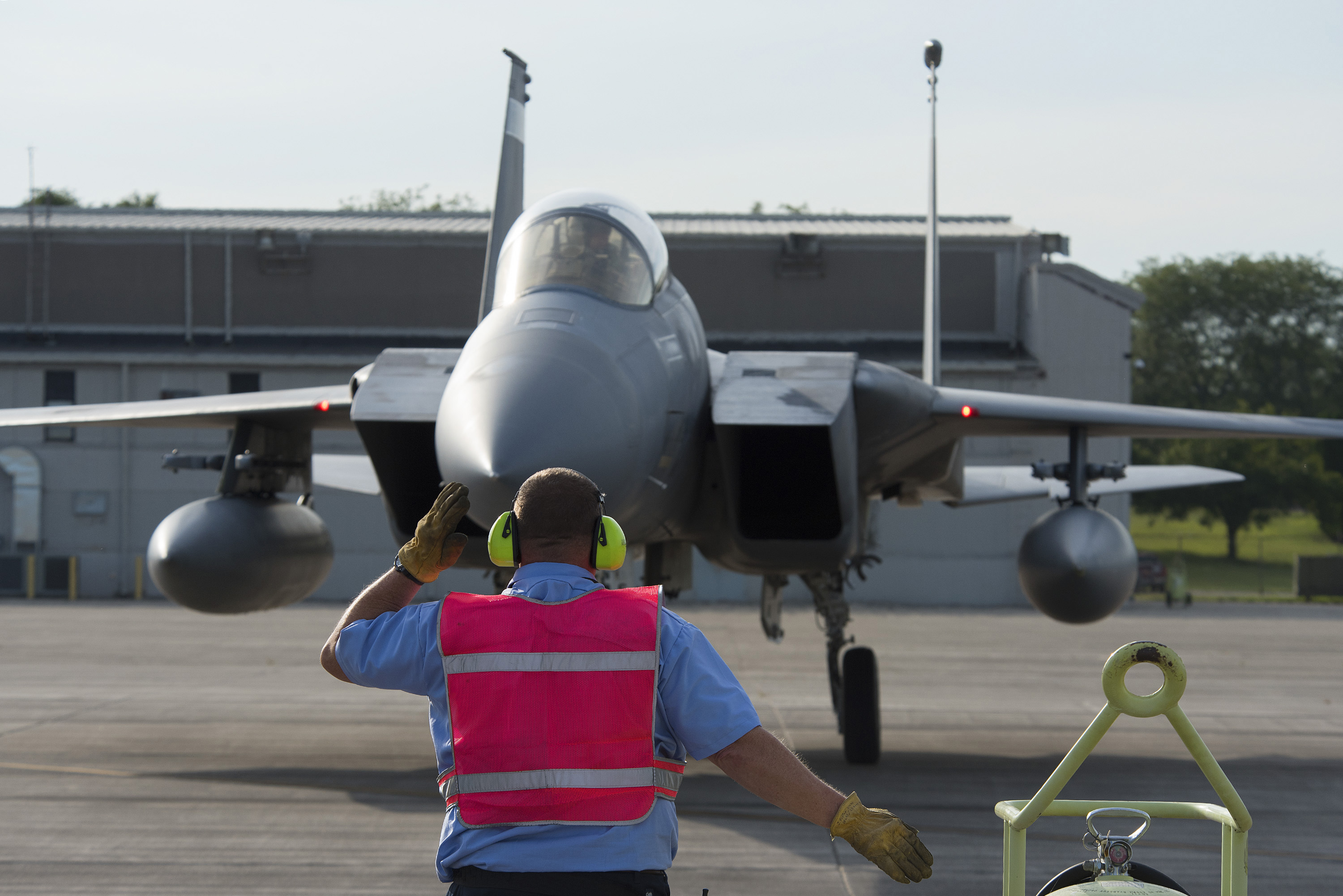 An 88th Logistics Readiness Squadron technician marshals a Florida Air National Guard F-15 Eagle to its parking place at Wright-Patterson Air Force Base, Ohio. Photo via U.S. Air Force/R.J. Oriez.