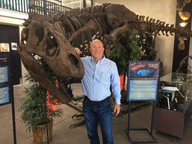 "NVision president Steve Kersen stands beside a Tyrannosaurus rex skeleton, part of the temporary ""Dinosaurs and Meteorites"" exhibit at the Texas Through Time museum. Photo via NVision."