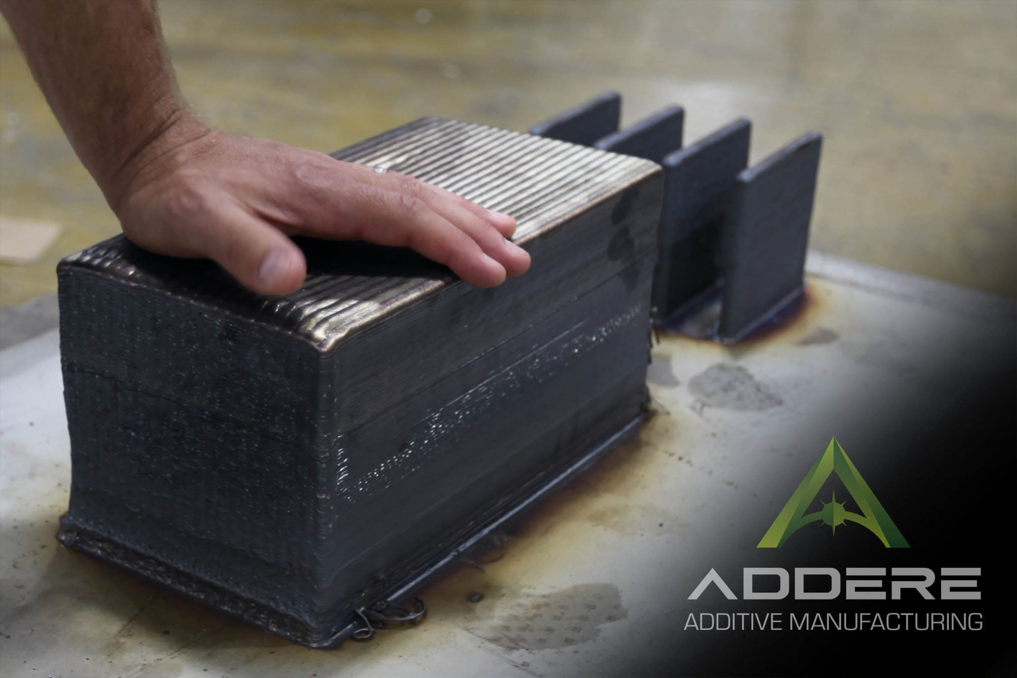 A 3D printed steel block with a machined section. Photo via ADDere.