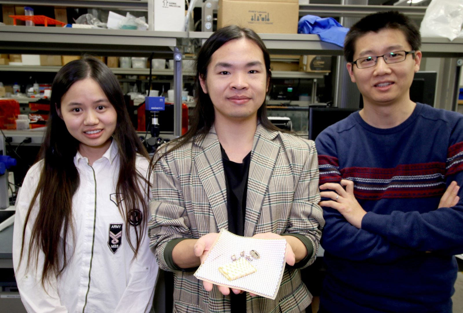 Assistant Professor of mechanical engineering Ling Li, right, with doctoral students Ting Yang, left, and Zhifei Deng, center, holding the 3D printed scale armour. Photo via Virginia Tech.