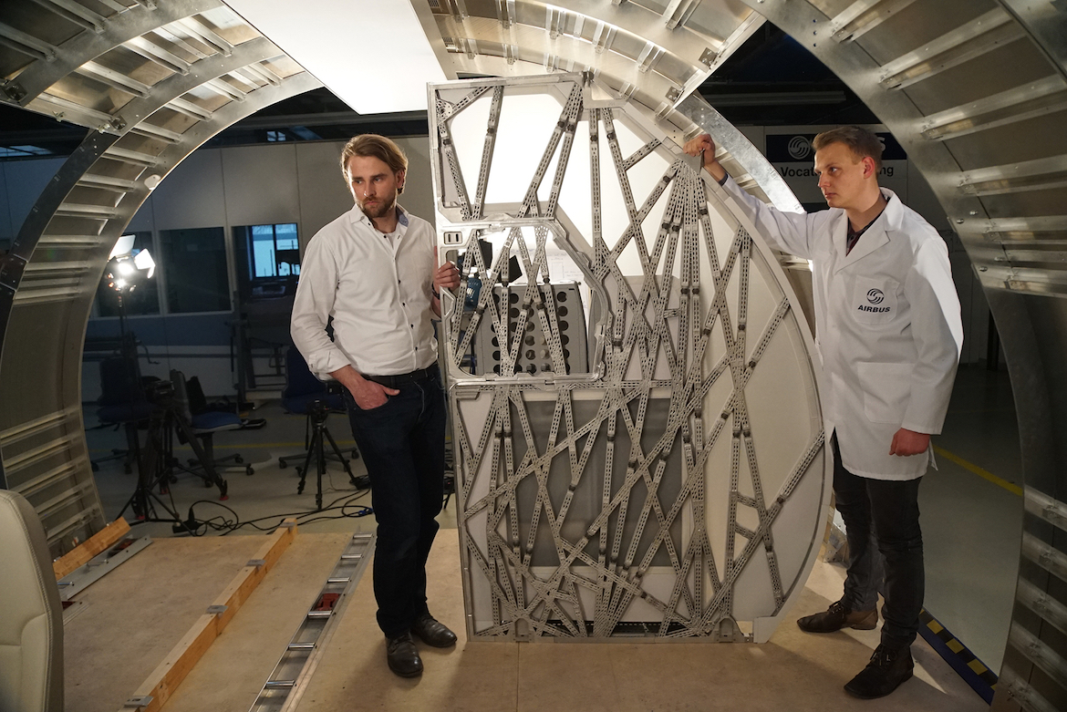 Airbus workers test placement of a bionic partition, its first generative design proof-of-concept. Photo via Airbus.