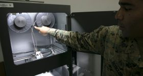 Quincy Reynolds with the Metal X 3D printer at Camp Kinser in Okinawa, Japan. Image via Stars and Stripes.