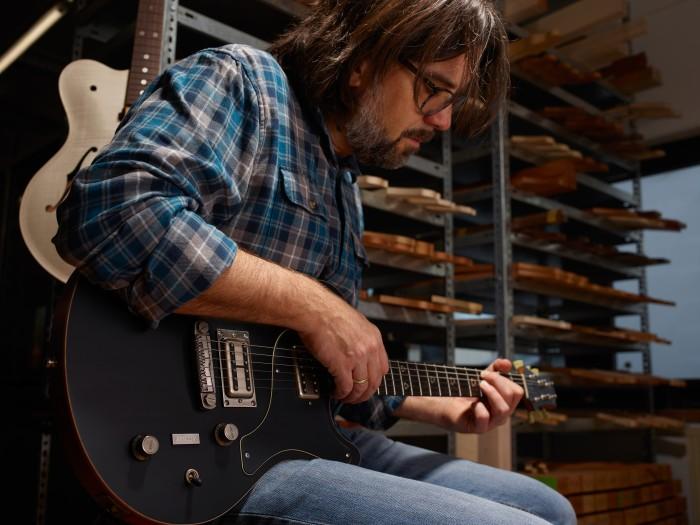 Nick Huber playing the guitar featuring the amorphous metal bridge. Photo via Heraeus.