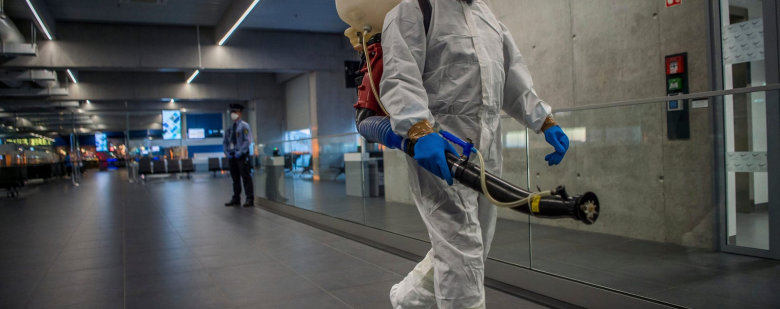 A worker carrying disinfection equipment at Budapest International Airport. Photo via Associated Press.