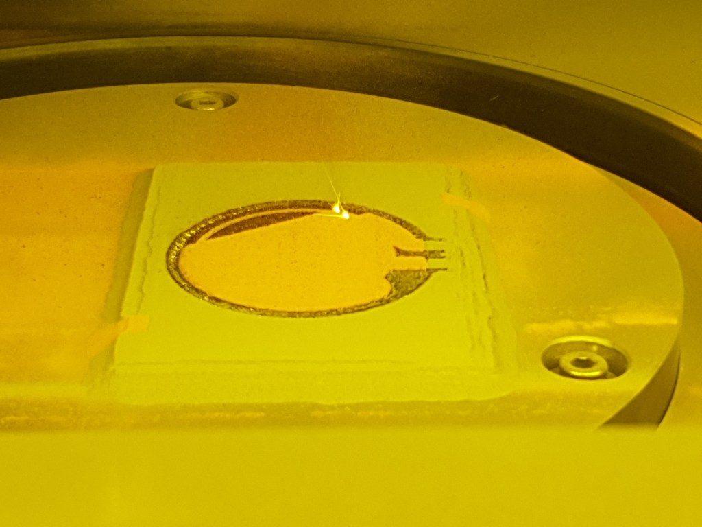 Multimetal part being 3D printed using the Aerosint recoater. Photo via Aerosint.