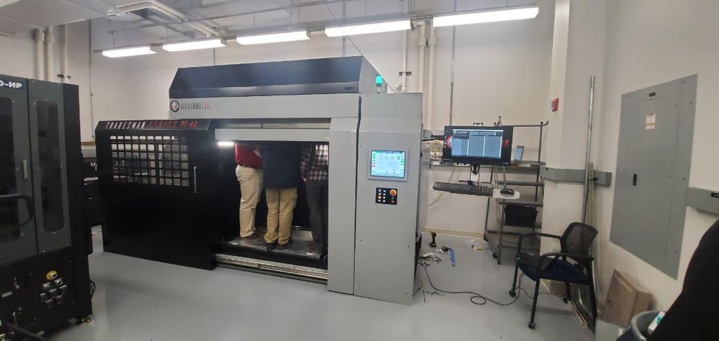 Two individuals inside JuggerBot's P3-44 FGF 3D printer. Photo via DSM.