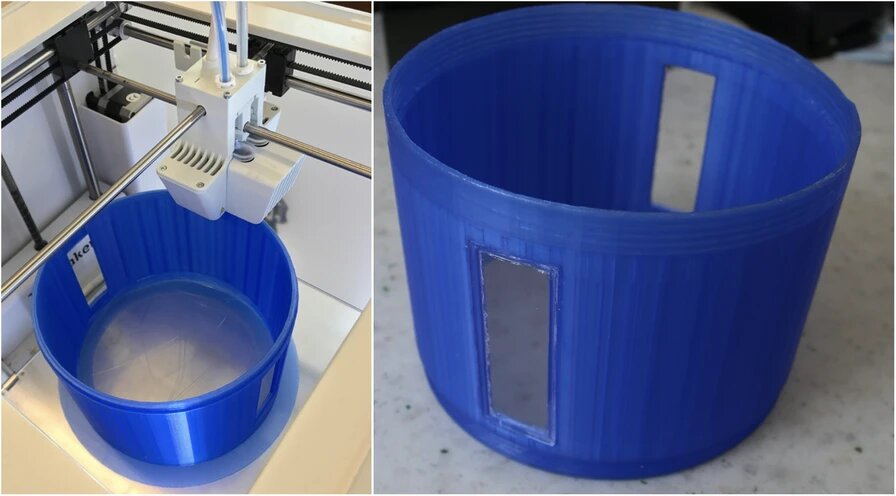 The 3D printing process of the chamber part with the viewing ports. Right: Photograph of the 3D printer during printing the chamber part with the two plexiglass windows glued in place. Image via 3D Printing in Medicine.