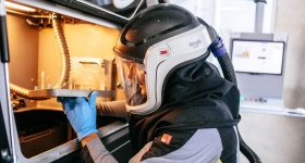 Engineer wearing PPE to transport an SLM fabricated part for cleaning. Photo via Materialise.