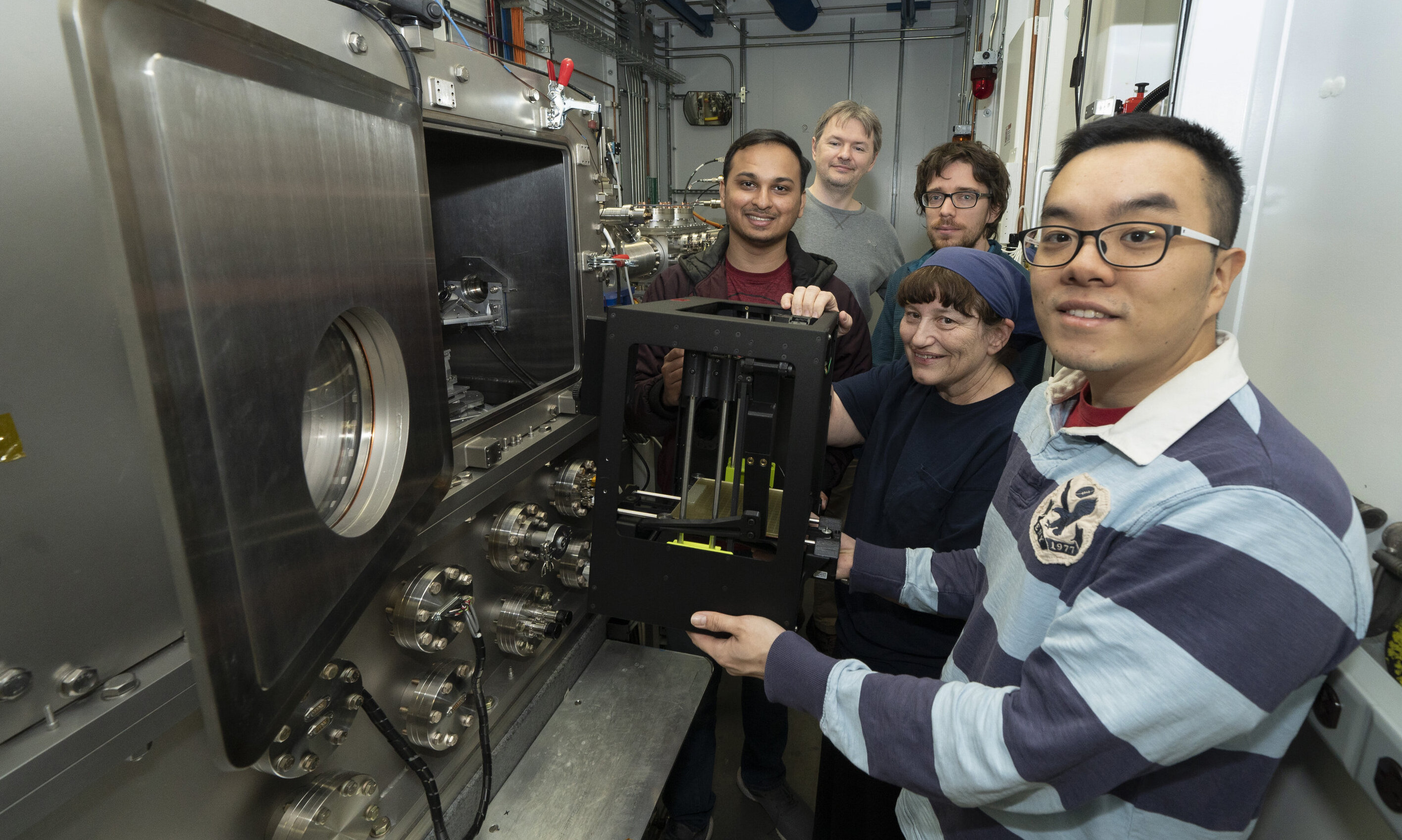 The research team placing their 3D printer into the chamber of the Soft Matter Interfaces (SMI) beamline at Brookhaven Lab's NSLS-II. Photo via BNL.