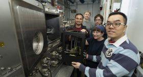 Featured image shows the research team placing their 3D printer into the chamber of the Soft Matter Interfaces (SMI) beamline at Brookhaven Lab's NSLS-II. Photo via BNL.