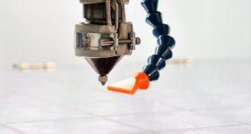 Featured image shows the dual extruder system used in Titan's Atlas-H 3D printers. Photo via Titan Robotics.