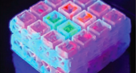 Featured image shows a collection of the researchers' microcages, covered in luminescent bio-gel. Image via the Advanced Materials journal.