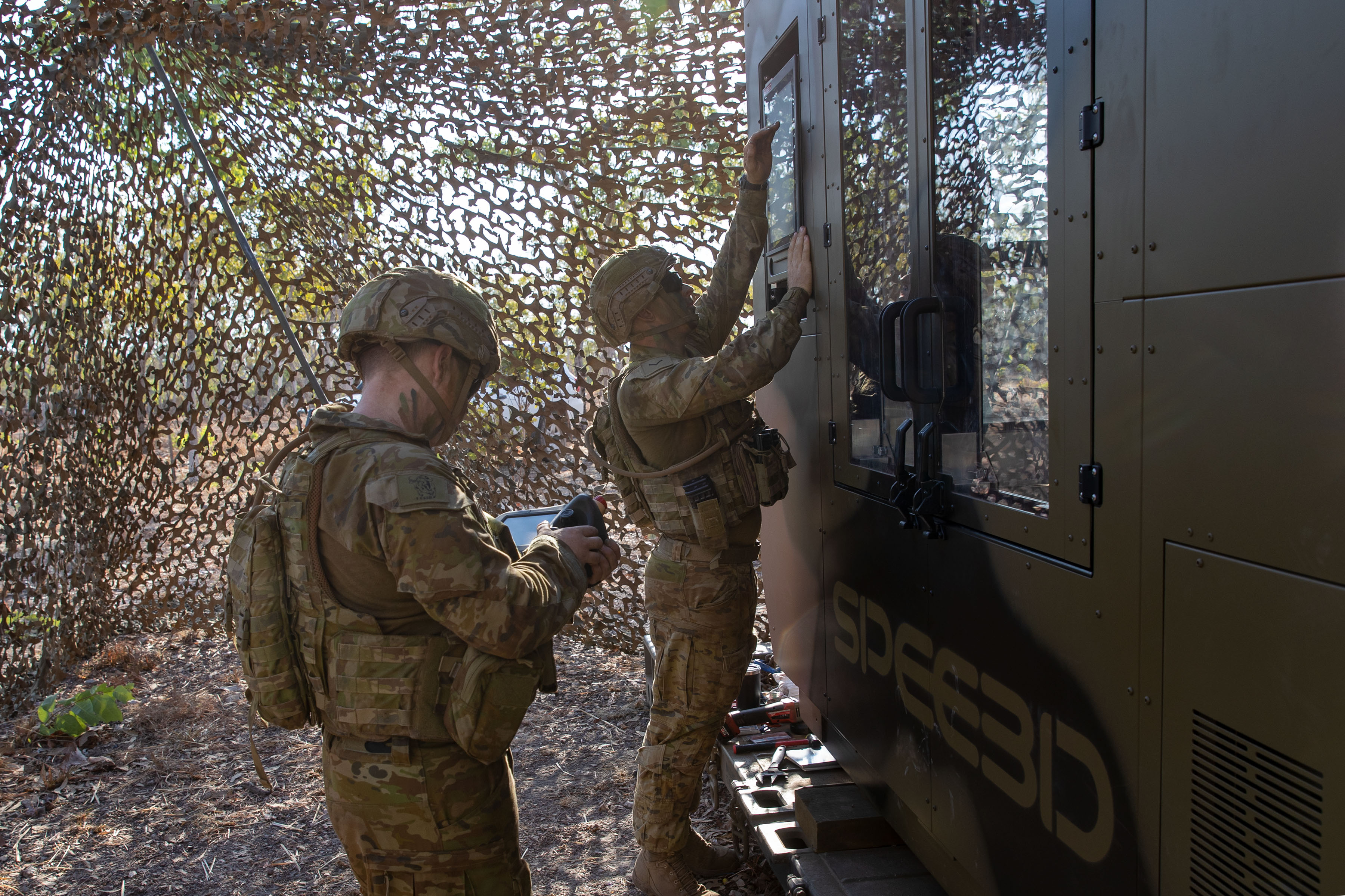 Australian Army Lance Corporal Sean Barton (right) and Craftsman Naythan Ryan, from the 1st Combat Service Support Battalion, preparing the WarpSPEE3D printer for operation. Photo via the Australian Army.