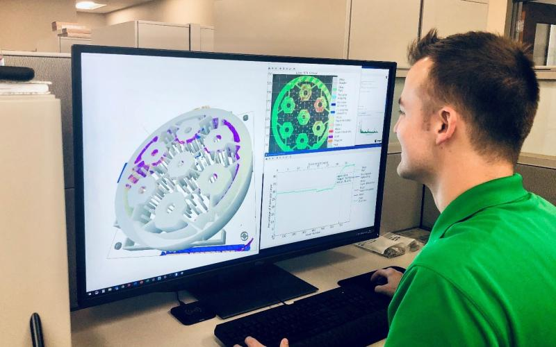Researcher Chase Joslin using the Peregrine software to monitor and analyze a component being 3D printed. at ORNL. Photo via Luke Scime/ORNL.