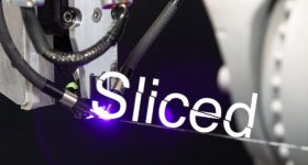 Featured image shows the Sliced logo on top of a Continuous Composites carbon laser. Image via Continuous Composites.