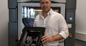 Stefan Kammann and an ESD-compliant gluing jig 3D Printed in Stratasys' ABS-ESD7 material. Photo via Stratasys.