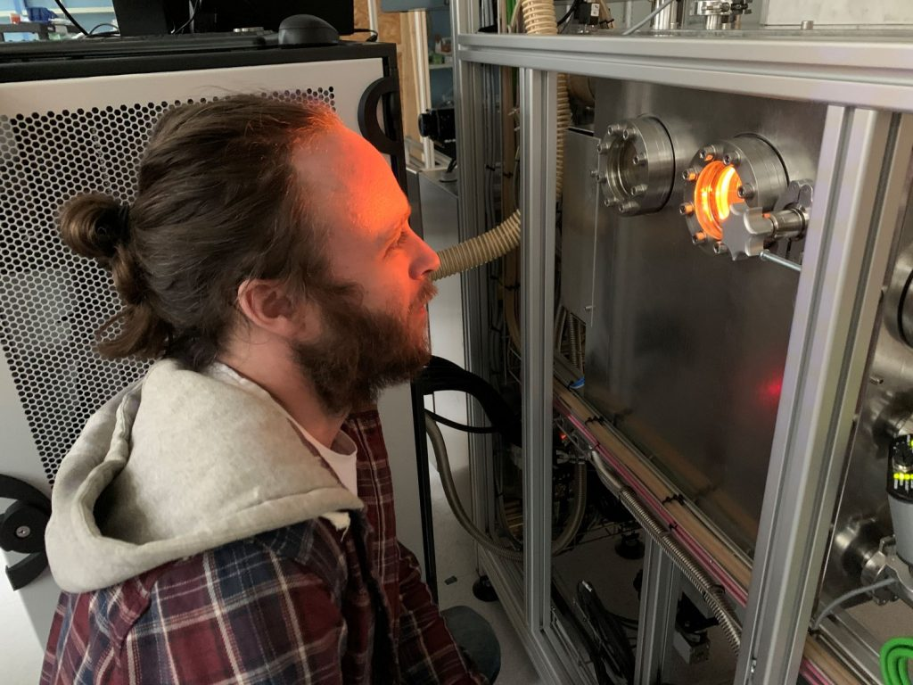 An engineer observing Freemelt's ONE 3D printer in operation.