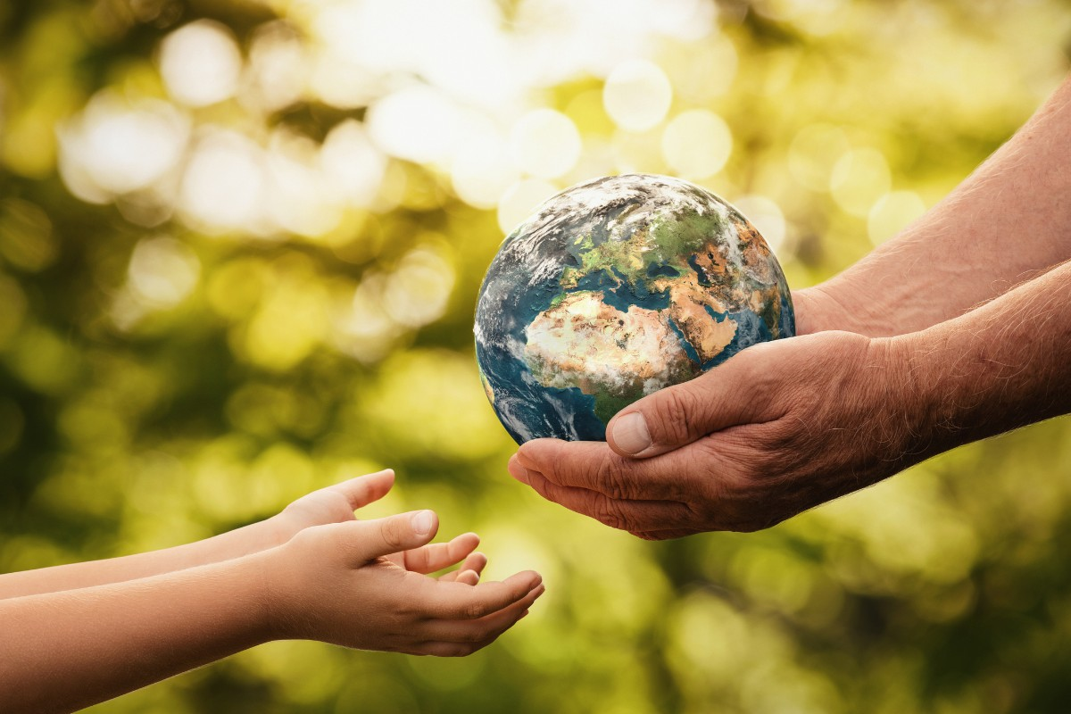Featured image shows a stock image of an adult handing a child a miniature planet Earth. Image via DSM.