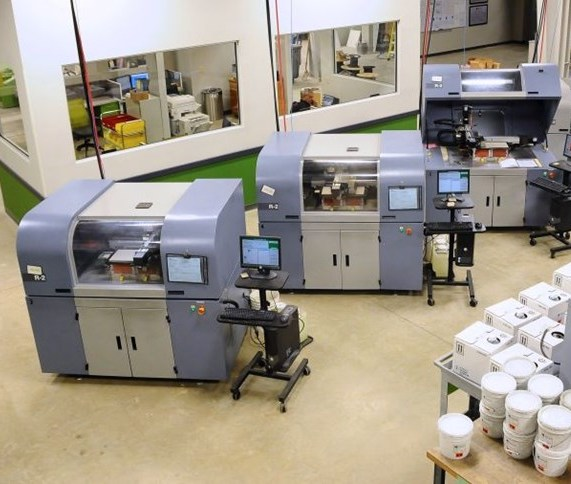 Featured image shows a line of ExOne's 3D printers that have been installed by a client in North America. Photo via ExOne.