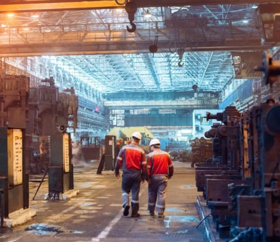 Featured image shows two engineers walking through a manufacturing facility. Photo via MxD.