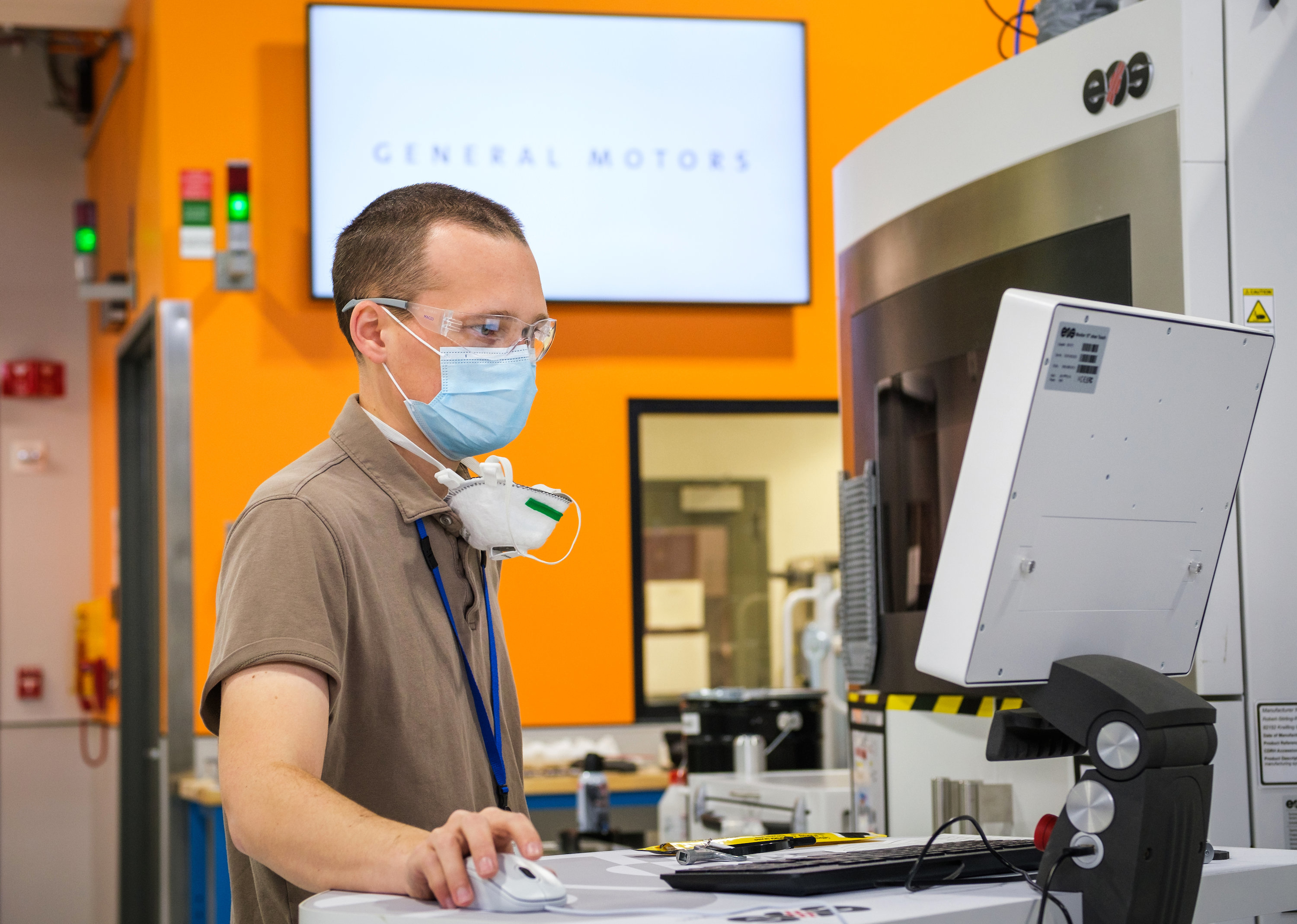 Featured image shows GM's Manufacturing Engineer Benjamin LeBlanc inspecting a 3D printer at the Additive Industrialization Center. Photo via GM.