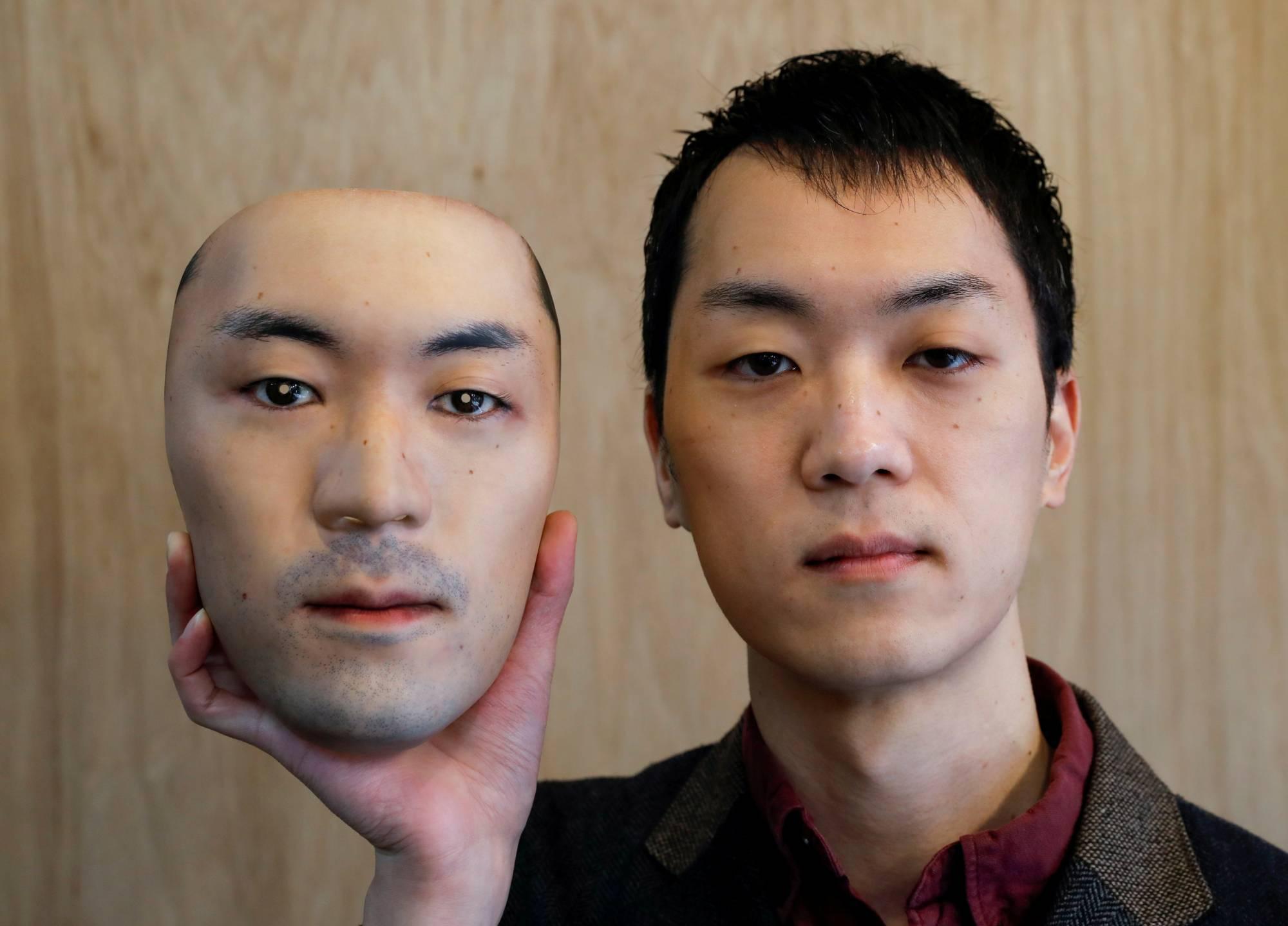 Shuhei Okawara, 30, holding a mask of his own face. Photo via Shuhei Okawara.