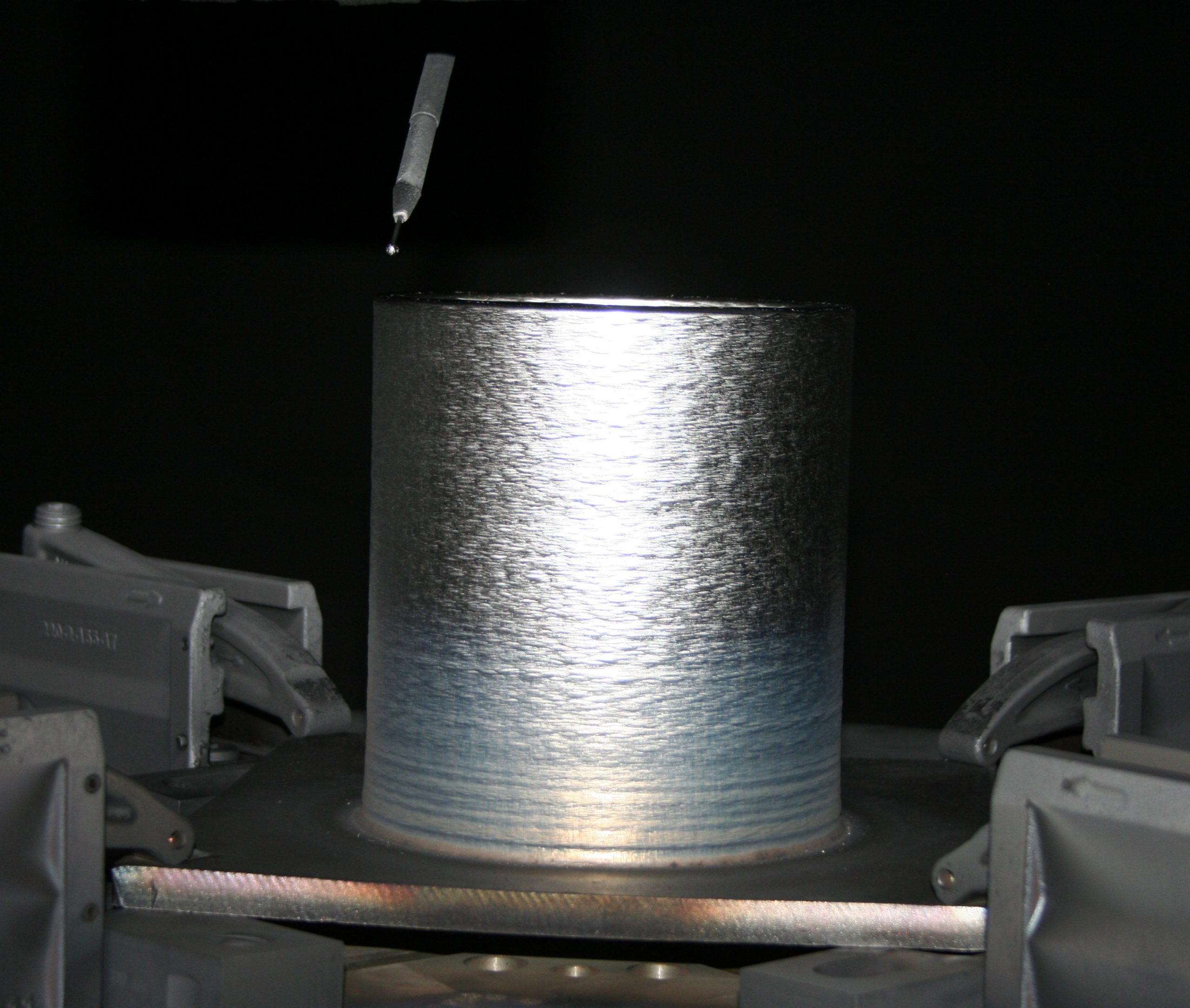 One of Sciaky's EBAM systems 3D printing a cylindrical structure.