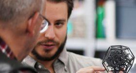 A Sinterit engineer teaching a client about a 3D printed part.