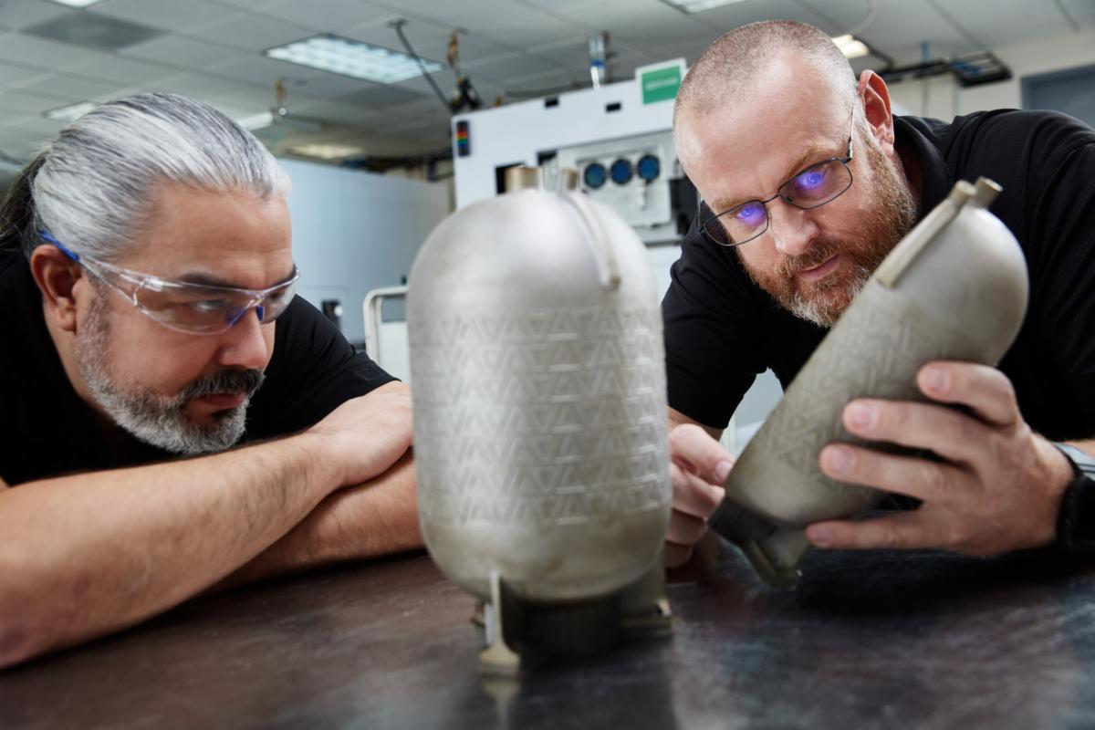 Engineers examine a titanium fuel tank printed on a VELO3D additive manufacturing system with no internal supports. Such tanks/pressure vessels are designed for use in aerospace and defense applications. Photo via VELO3D.