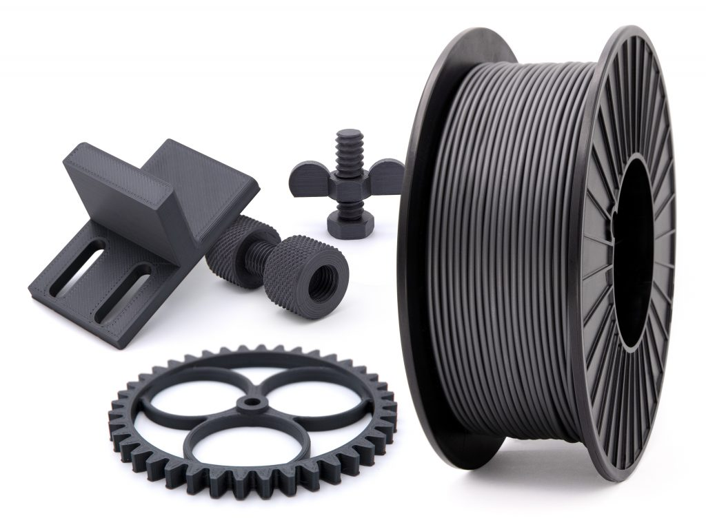 A spool of Jabil's new PA 0600 filament alongside a set of printed parts.