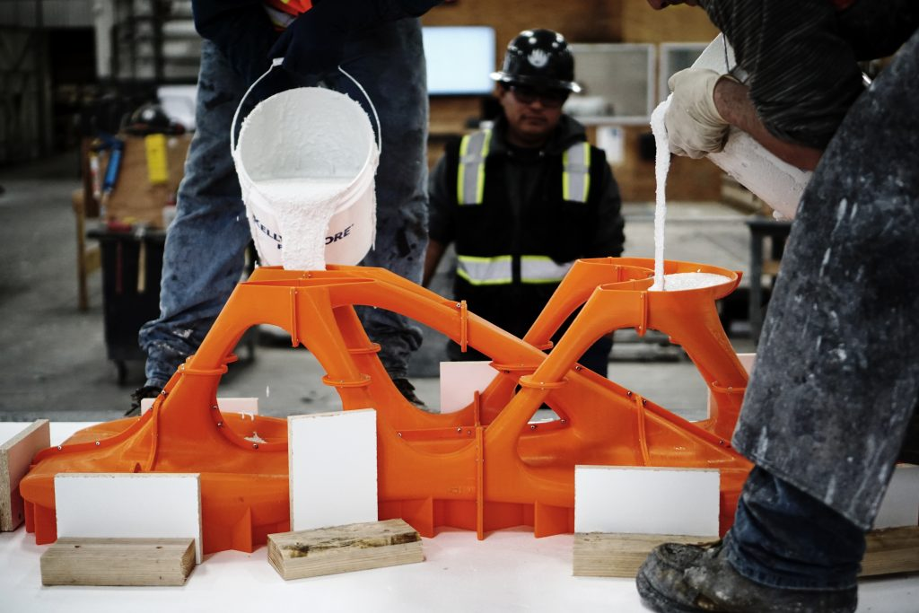 Filling the 3D printed mold with white concrete. Photo via Slicelab.