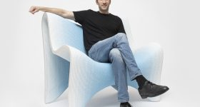 Designer Philipp Aduatz sitting on his 3D printed gradient fauteuil.