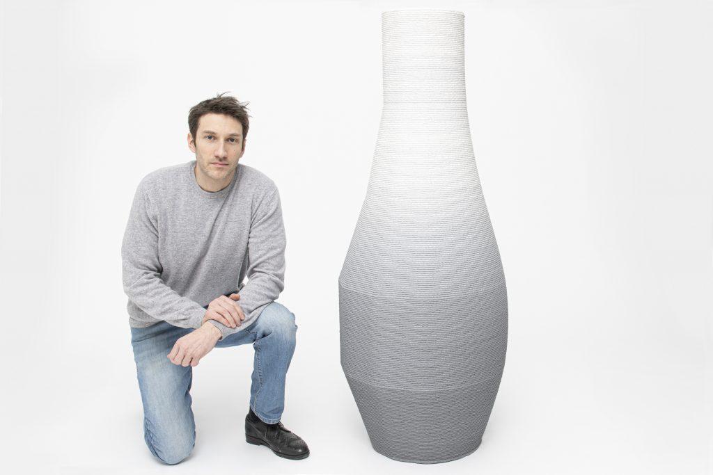 Designer Philipp Aduatz kneeling next to his 3D printed gradient vase.
