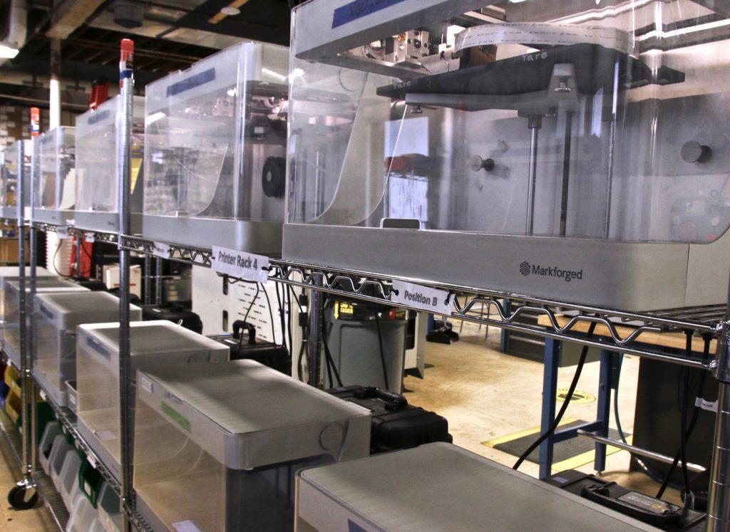 A print farm of Markforged 3D printers.