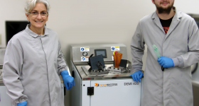 Primary Manufacturing lab technician Lisa Baker and engineering technician Gage Tift with the PostProcess DEMI 430 system. Photo via PostProcess Technologies.