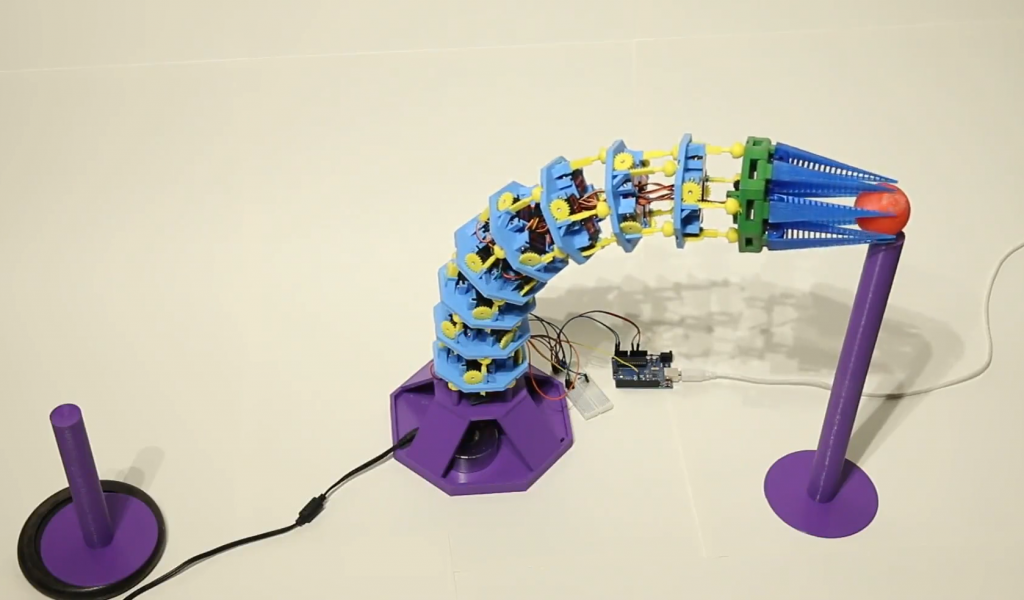 The robot learning to pick up and place marbles. Photo via University of Tübingen.